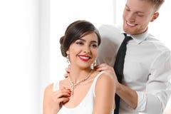 Man som sätter eleganta smycken på härlig kvinna arkivbild