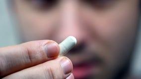 Man som sätter en preventivpiller i hans mun royaltyfri foto