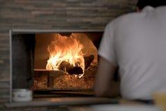 Man som in sätter Lahmacun deg till den varma stenen Oven With Wooden Pizza Peel Arkivbilder