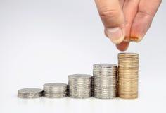Man som sätter myntet till den stigande bunten av mynt Arkivbild