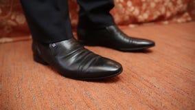 Man som sätter på hans läderskor piska skor close upp stock video