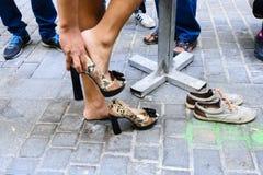 Man som sätter på skor för höga häl Royaltyfri Foto