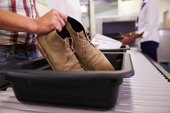 Man som sätter skor in i Tray For Airport Security Check Royaltyfri Foto
