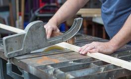 Man som sågar ett stycke av trä för ett DIY-projekt royaltyfri foto