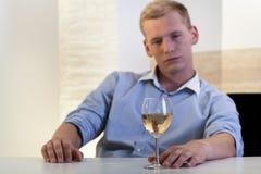 Man som söker efter ett exponeringsglas av vin Arkivfoto
