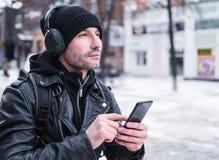 Man som söker efter ett ställe genom att använda GPS översikten i smartphone Honom som är borttappad i okänd stad han är iklädd e Arkivbilder