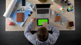 Man som söker efter intressanta apps på minnestavlan med den gröna skärmen, digital värld royaltyfria foton