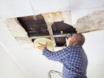 Man som samlar vatten i handfat från tak Arkivfoton
