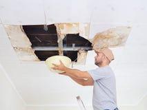 Man som samlar vatten i handfat från tak Damag för takpaneler Royaltyfri Bild