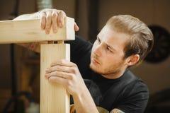 Man som sammanfogar två delar av träplankor Arbetarsnickareföreningsmänniska Royaltyfri Bild