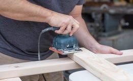 Man som sandpapprar ett DIY-projekt arkivfoto