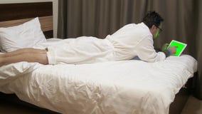 Man som ser data på den digitala minnestavlan Mannen i hotell ligger på säng och användatouchpaden arkivfilmer