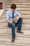Man som ser den smart tableten som sitter på trappa Arkivfoton