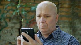 Man som ser eftertänksam till mobiltelefonen med en besviken framsida arkivfoto