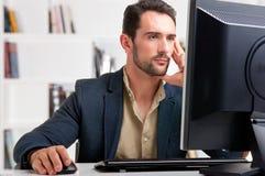 Man som ser en datorbildskärm Arkivbild