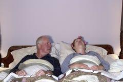 Man som ser förskräckt på frun i säng Royaltyfri Bild