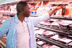 Man som ser gods i livsmedelsbutikavsnitt, medan shoppa arkivfoton
