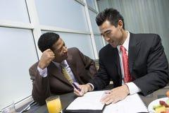 Man som ser hans undertecknande dokument för affärspartner Royaltyfri Foto
