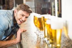 Man som ser ner uppställda öl Arkivfoton