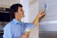 Man som ser på kylskåpet Fotografering för Bildbyråer