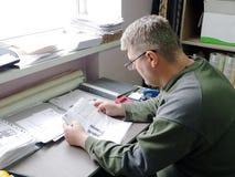 Man som ser papper i exponeringsglas royaltyfri foto