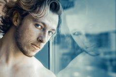 Man som ser reflexion i exponeringsglas royaltyfria bilder