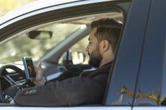Man som ser smartphonen, når att ha parkerat hans bil royaltyfri foto