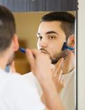 Man som ser spegeln och rakar framsidan med rakkniven Royaltyfri Bild