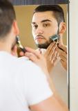 Man som ser spegeln och rakar framsidan med rakkniven arkivbilder