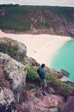 Man som ser till den Porthcurno stranden arkivfoton