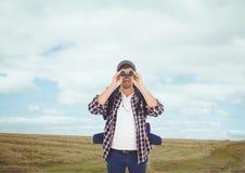 Man som ser till och med kikare mot landskapbakgrund fotografering för bildbyråer