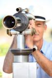 Man som ser till och med teleskopet Royaltyfri Foto