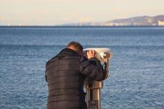 Man som ser till och med turist- kikare Royaltyfria Bilder