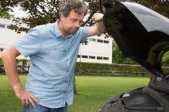 Man som ser under den Hood Of Breakdown Car skåpbilen Royaltyfria Bilder