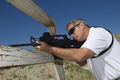 Man som siktar geväret på skjutavstånd arkivbild