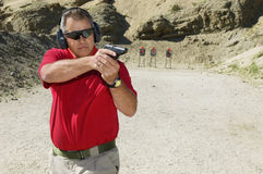 Man som siktar handvapnet på skjutavstånd arkivbilder