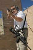 Man som siktar handvapnet på skjutavstånd royaltyfri bild