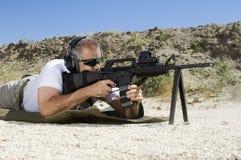 Man som siktar maskingeväret på skjutavstånd arkivfoto