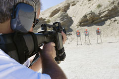 Man som siktar maskingeväret på skjutavstånd arkivbild