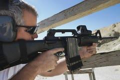 Man som siktar maskingeväret på skjutavstånd royaltyfria bilder