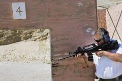 Man som siktar maskingeväret på skjutavstånd royaltyfri fotografi