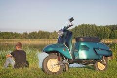 Man som sitter nära återställt grönt retro mopedanseende på en äng i eftermiddagen Arkivbild