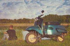 Man som sitter nära återställt grönt retro mopedanseende på en äng i eftermiddagen Royaltyfria Foton