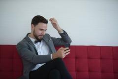 Man som sitter och använder en smart telefon royaltyfria bilder