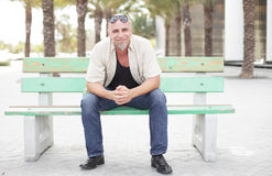 Man som sitter på en hållplatsbänk fotografering för bildbyråer