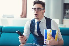 Man som sitter på en soffa, hållande ögonen på TV och att rymma fjärrkontroll- och popcornasken som förvånas på vad han ser arkivfoto