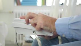 Man som sitter på en stol i talande telefonaffär för mötesrum genom att använda en landline arkivfilmer