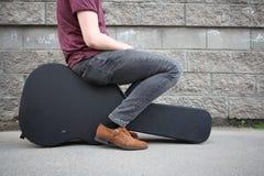 Man som sitter på ett svart gitarrfall H?rt fall f?r elektrisk gitarr royaltyfri bild