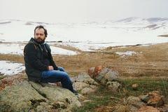 Man som sitter på stenarna och ser vinternaturen royaltyfria foton