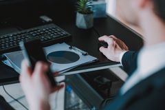 Man som sitter på tabellen och sätter assistenten på datormus royaltyfria foton